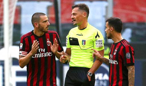 AC Milan defender Leonardo Bonucci, left, speaks with referee Piero Giacomelli, center, after receiving a red card during a Serie A soccer match between AC Milan and Genoa, at the Giuseppe Meazza stadium in Milan, Italy, Sunday, Oct. 22, 2017. Bonucci was sent off in the first half of Milan's 0-0 draw at home with Genoa on Sunday for elbowing a defender in the head as he jostled for position on a free kick. (Matteo Bazzi/ANSA via AP)