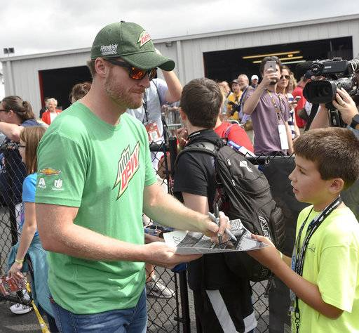 Driver Dale Earnhardt Jr. gives autographs to racing fans before a NASCAR Talladega auto race at Talladega Superspeedway, Sunday, Oct. 15, 2017, in Talladega, Ala. (AP Photo/Albert Cesare)