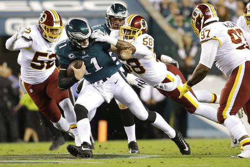 Washington Redskins linebacker Junior Galette (58) grabs at the facemask of Philadelphia Eagles quarterback Carson Wentz (11) during the first half of an NFL football game, Monday, Oct. 23, 2017, in Philadelphia. Galette and the Redskins were penalized for the infraction.