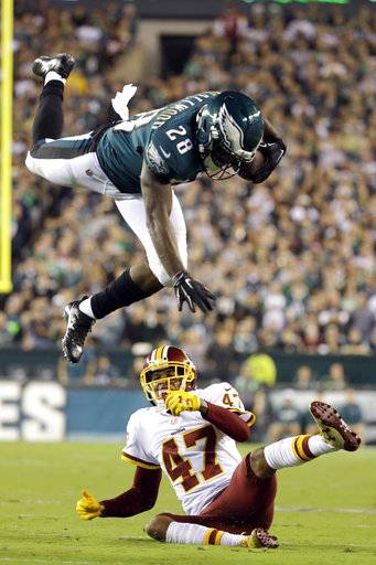 Philadelphia Eagles running back Wendell Smallwood (28) goes airborne while trying to avoid a tackle by Washington Redskins cornerback Quinton Dunbar (47) during the first half of an NFL football game, Monday, Oct. 23, 2017, in Philadelphia.