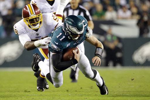 Philadelphia Eagles quarterback Carson Wentz (11) dives forward as Washington Redskins linebacker Junior Galette (58) tries to stop him during the second half of an NFL football game, Monday, Oct. 23, 2017, in Philadelphia.