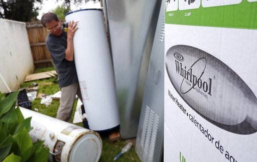 FILE — In this Sunday, March 22, 2015, file photo, a repairman installs a Whirlpool water heater at a home in Los Angeles. Sears will no longer sell Whirlpool appliances, ending a business partnership that dates make more than 100 years. (AP Photo/Richard Vogel, File) The Associated Press