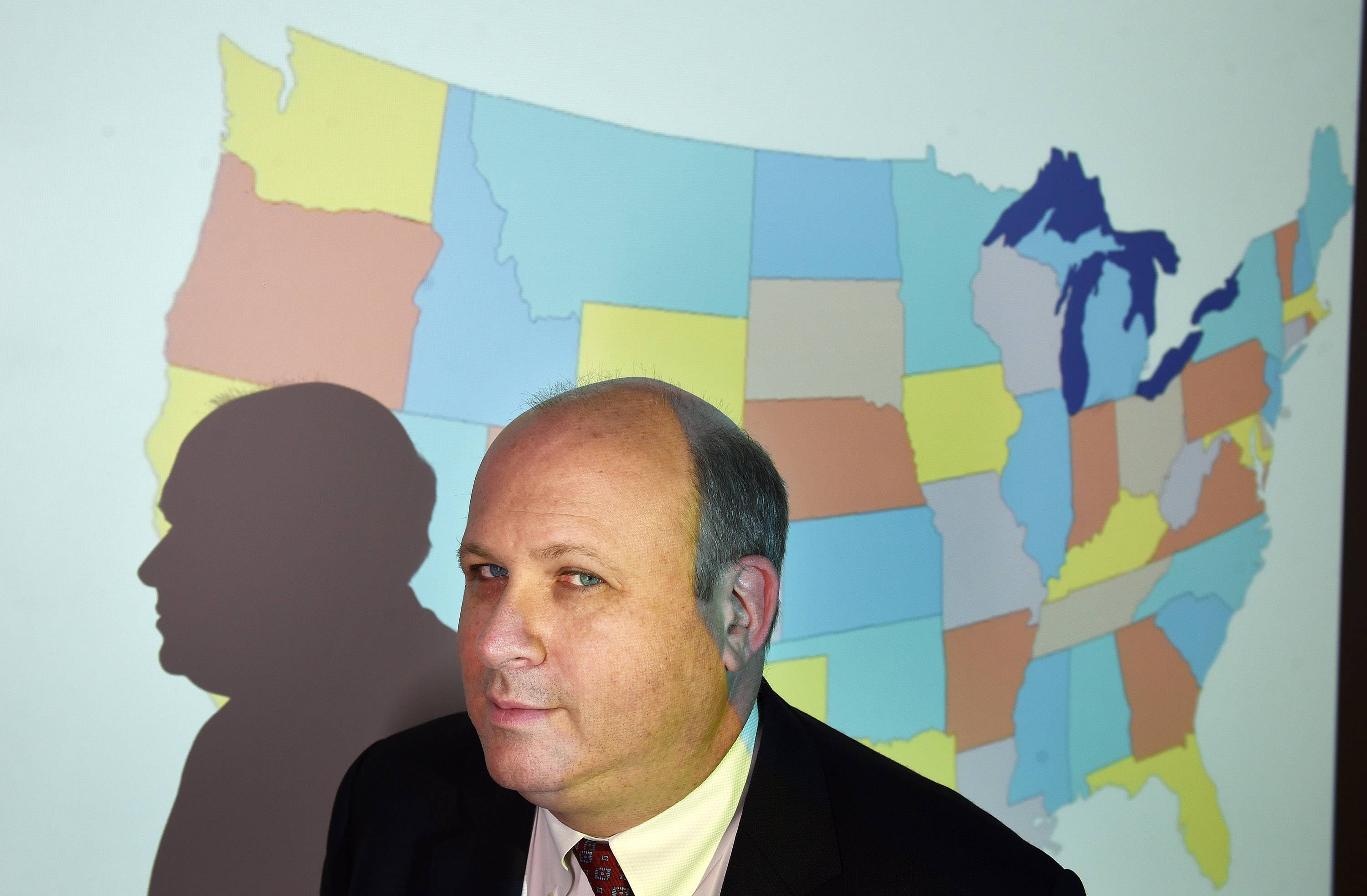 Marc Elias of Perkins Coie poses for a portrait in front of a projected map of the United States at the firm in April 2016 in Washington.