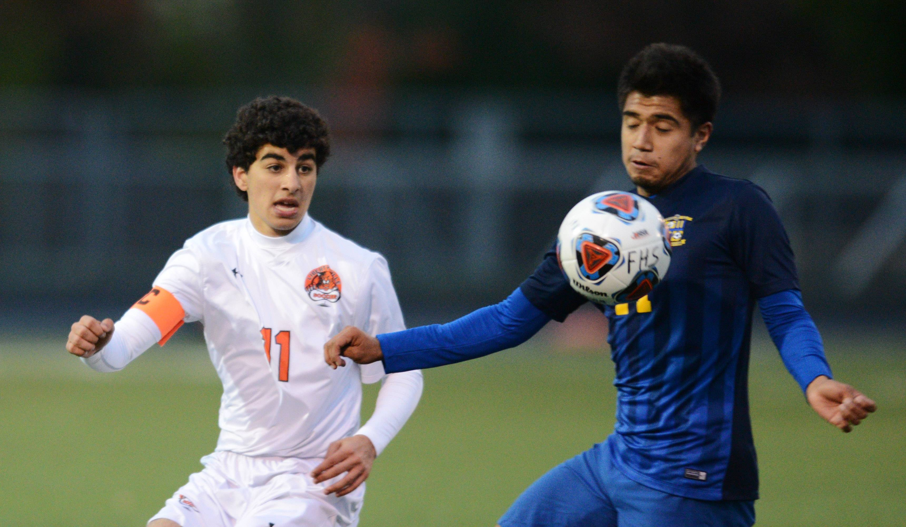 Wheeling's Robert Cruz, right, keeps the ball in front of himself as Libertyville's Riley Hoff closes in during the Fremd boys soccer sectional semifinal in Palatine on Tuesday.