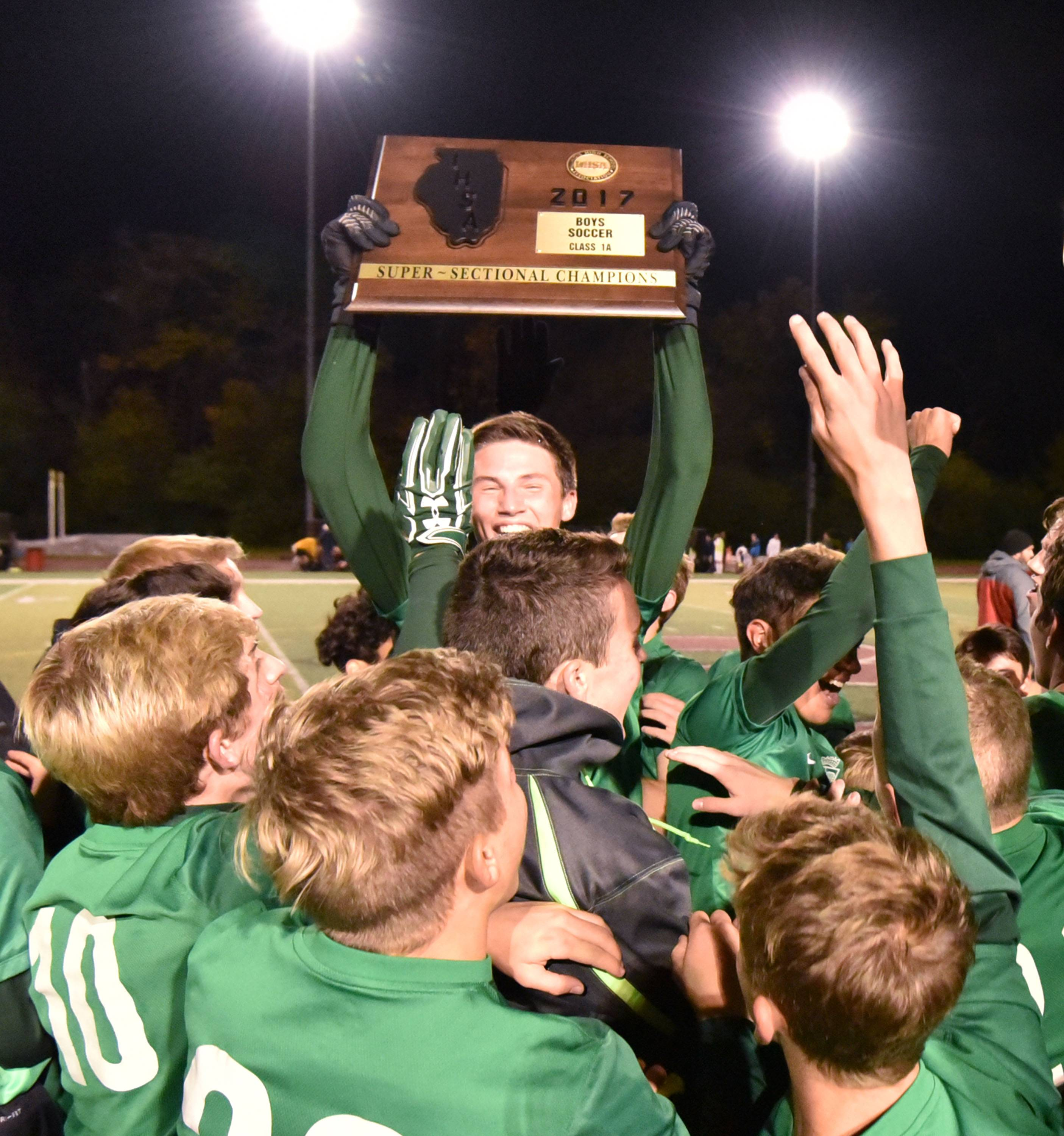 St. Edward team captain A.J. Franklin holds the championship trophy after the Green Wave defeated Francis Parker Tuesday in the Class 1A Benedictine boys soccer supersectional in Lisle.