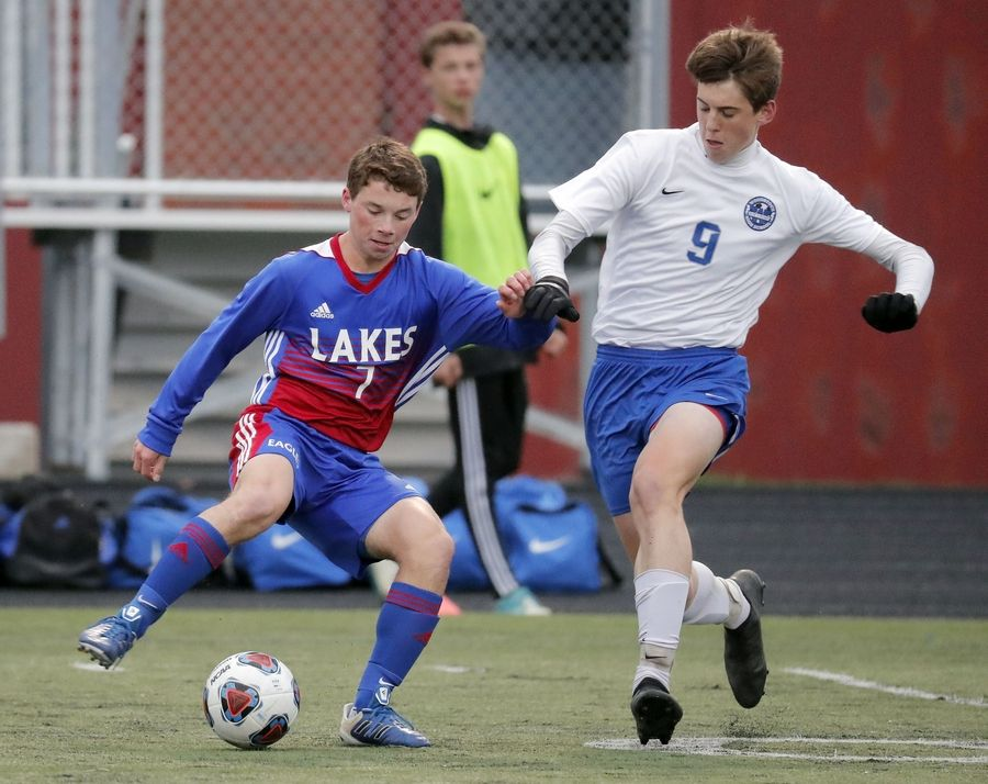 Lakes' Andrew Gaetano, left, and Woodstock's Ryan Azzaline battle during Class 2A Grayslake Central boys soccer sectional semifinal play Tuesday.
