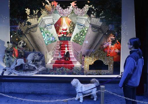FILE - In this Nov. 18, 2013, file photo, a woman walks her dog past a vintage Santa Claus holiday window display at Lord & Taylor department store in New York. A real estate startup called WeWork Cos. is announcing a deal to buy Lord & Taylor's storied flagship in Manhattan for $850 million. The transaction, announced Tuesday, Oct. 24, 2017, is part of an overall plan by Lord & Taylor's parent Hudson's Bay Co. to pare down its debt and reinvigorate the chain. (AP Photo/Mark Lennihan, File)
