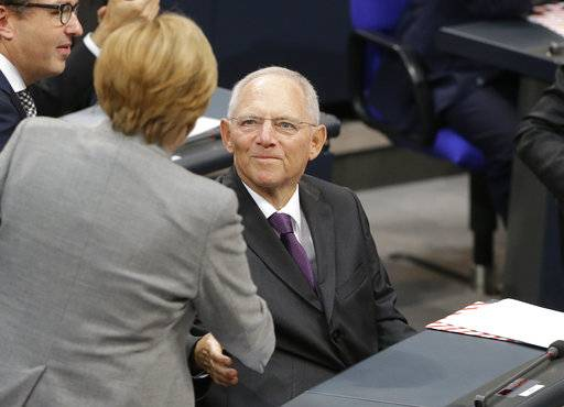 New German Parliament President Wolfgang Schaeuble is congratulated by German Chancellor Angela Merkel during the first meeting of the German parliament after the election in Berlin, Germany, Tuesday, Oct. 24, 2017. (AP Photo/Ferdinand Ostrop)