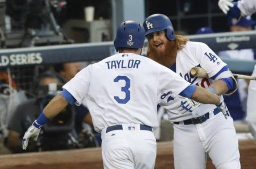 Los Angeles Dodgers' Chris Taylor is congratulated by Justin Turner after hitting a home run during the first inning of Game 1 of baseball's World Series against the Houston Astros Tuesday, Oct. 24, 2017, in Los Angeles. (AP Photo/Alex Gallardo)