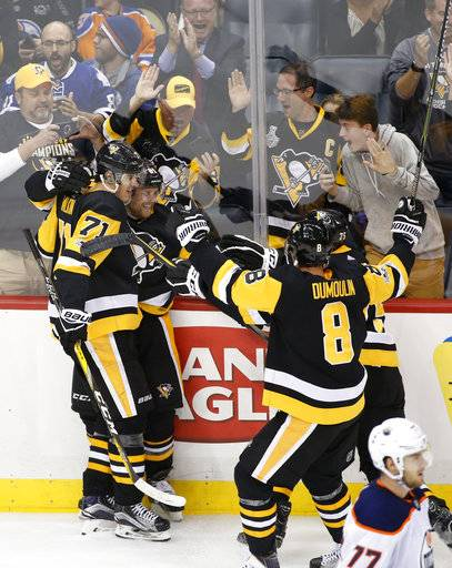 Pittsburgh Penguins' Phil Kessel, second from left, celebrates his game winning goal against the Edmonton Oilers in overtime with teammate Evgeni Malkin (71) at the end of an NHL hockey game in Pittsburgh, Tuesday, Oct. 24, 2017. The Penguins won 2-1. (AP Photo/Gene J. Puskar)