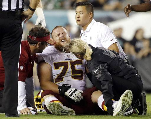 FILE - In this Monday, Oct. 23, 2017, file photo, trainers look examine Washington Redskins offensive guard Brandon Scherff (75) during the second half of an NFL football game against the Philadelphia Eagles in Philadelphia. The banged-up Redskins got some good news about Scherff's knee injury with coach Jay Gruden saying there's a chance Scherff can play Sunday against the Dallas Cowboys. Scherff sprained the MCL in his left knee and hurt his lower back, one of several Redskins injuries from a 34-24 loss at the Philadelphia Eagles on Monday night. (AP Photo/Matt Rourke, File)