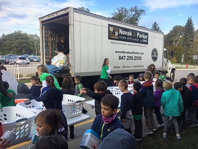 Preschool and first-grade students at Westbrook School for Young Learners load goods collected to aid in Puerto Rico hurricane relief on a truck for shipment to Chicago, where material is being assembled for a flight to Puerto Rico on a donated airplane.