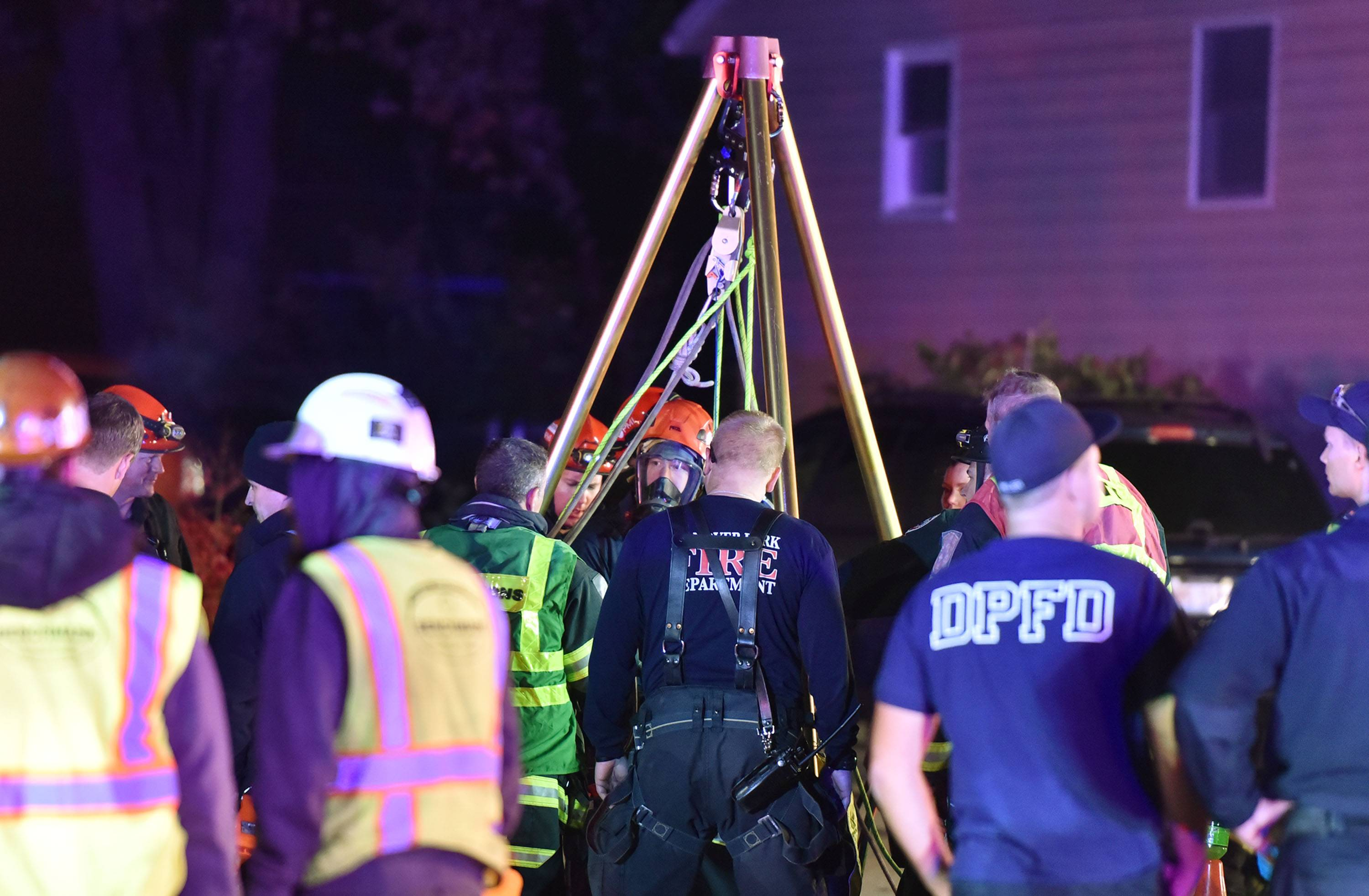 Emergency crews use a tripod to lower a rescue worker into a sewer line during the rescue effort on South Park Boulevard in Streamwood Wednesday night.