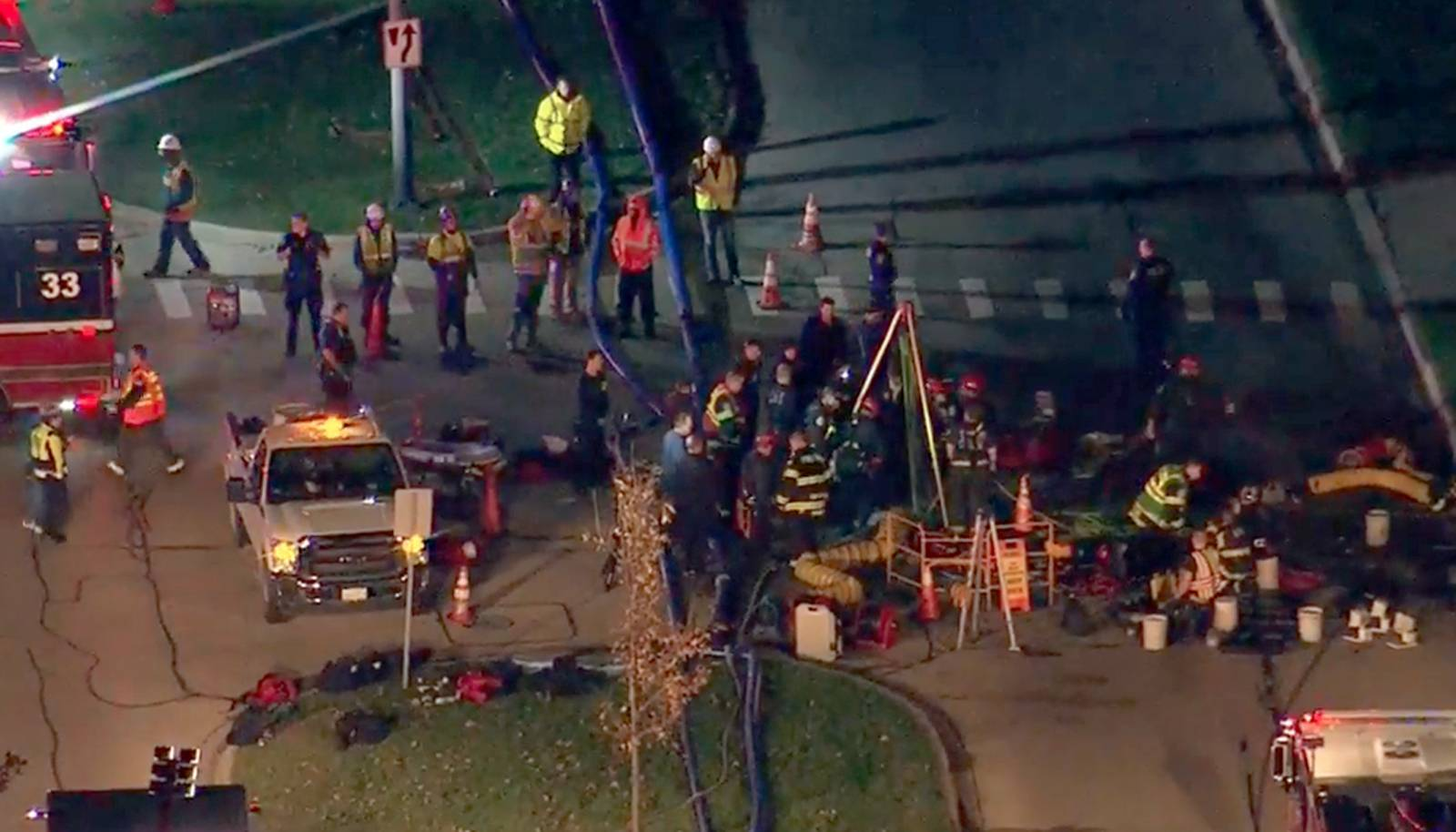 Rescue personnel work along Park Boulevard at the scene of a rescue in a manhole Wednesday evening in Streamwood.