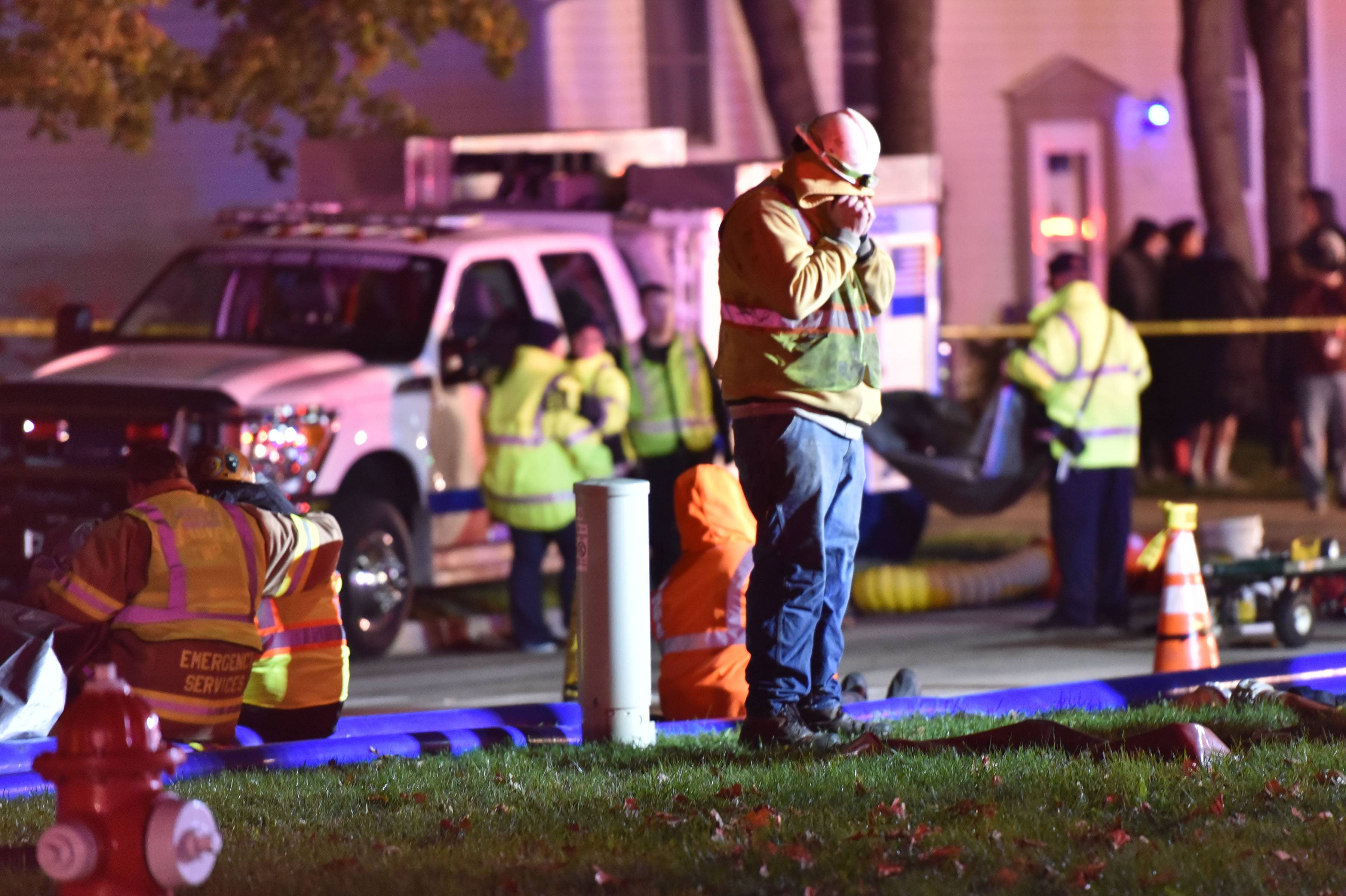 A man in a hard hat reacts after crews pulled a person from a sewer line on South Park Boulevard in Streamwood Wednesday night.