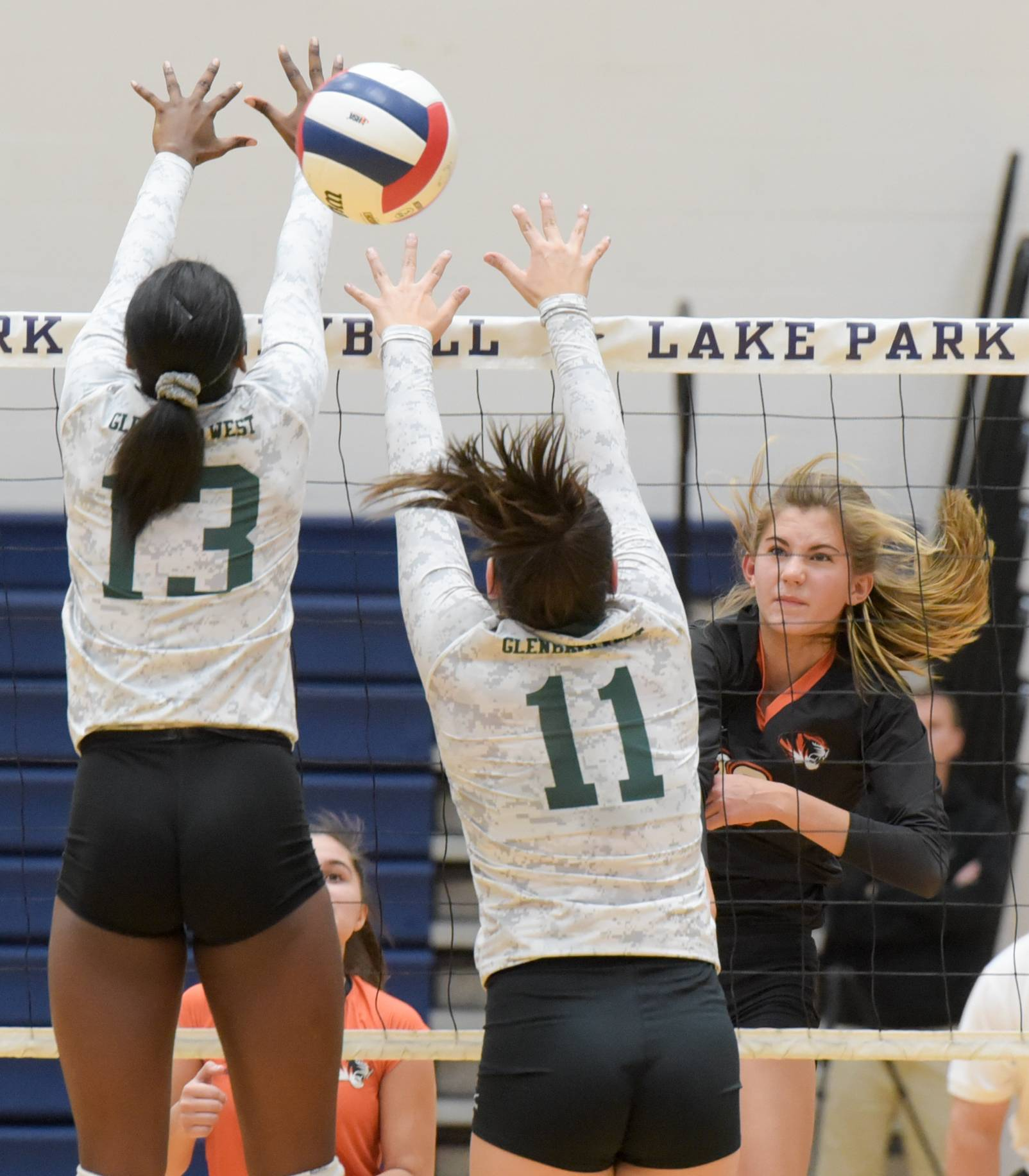 Wheaton Warrenville South's Zayna Meyer fires a shot past Glenbard West's Ananda Patterson and Kaityn Dumerer during the Class 4A Lake Park girls volleyball regional final.