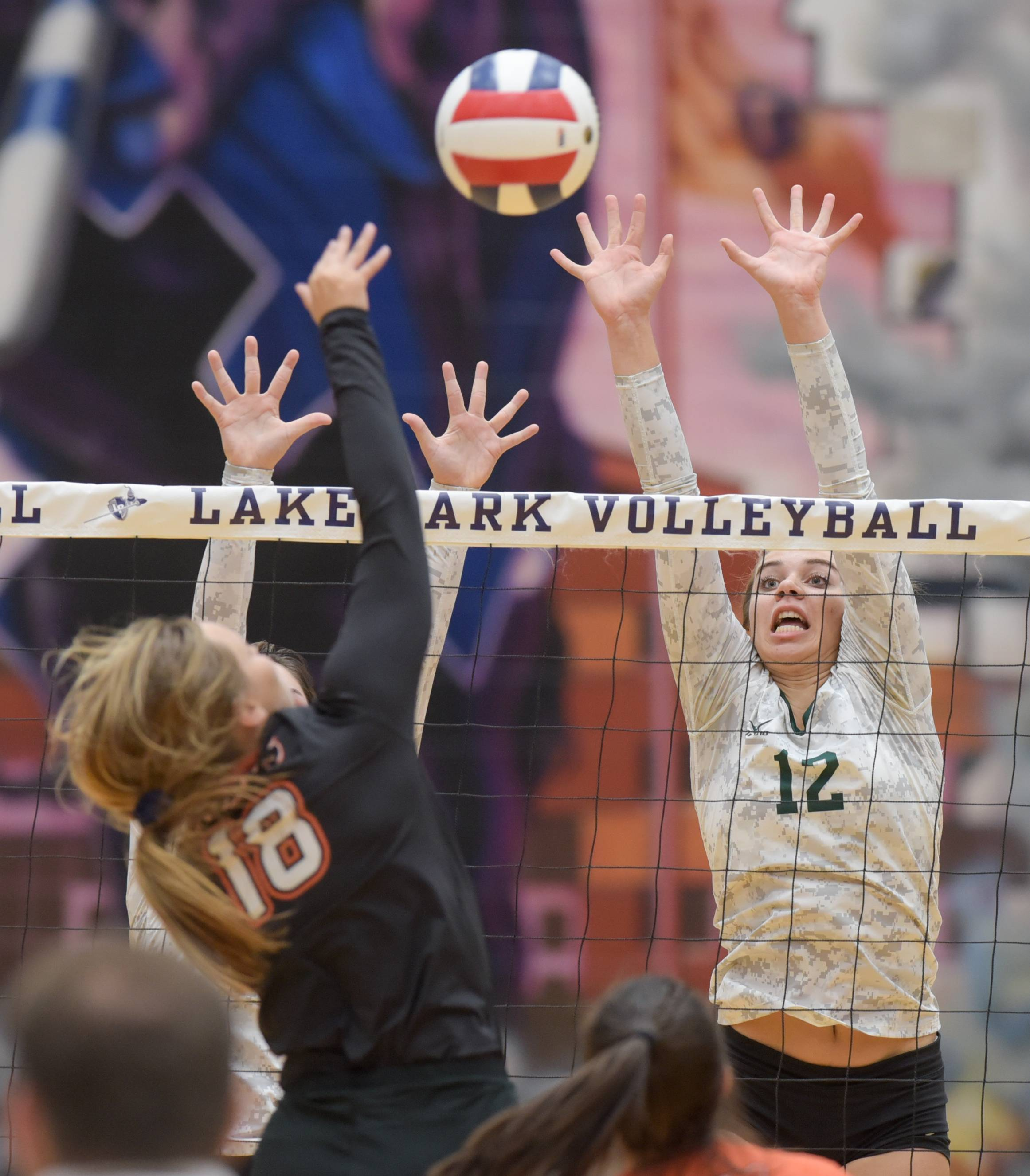 Glenbard West's Nina Crawford leaps to block a shot by Wheaton Warrenville South's Hannah Joyce during Class 4A Lake Park girls volleyball regional final.