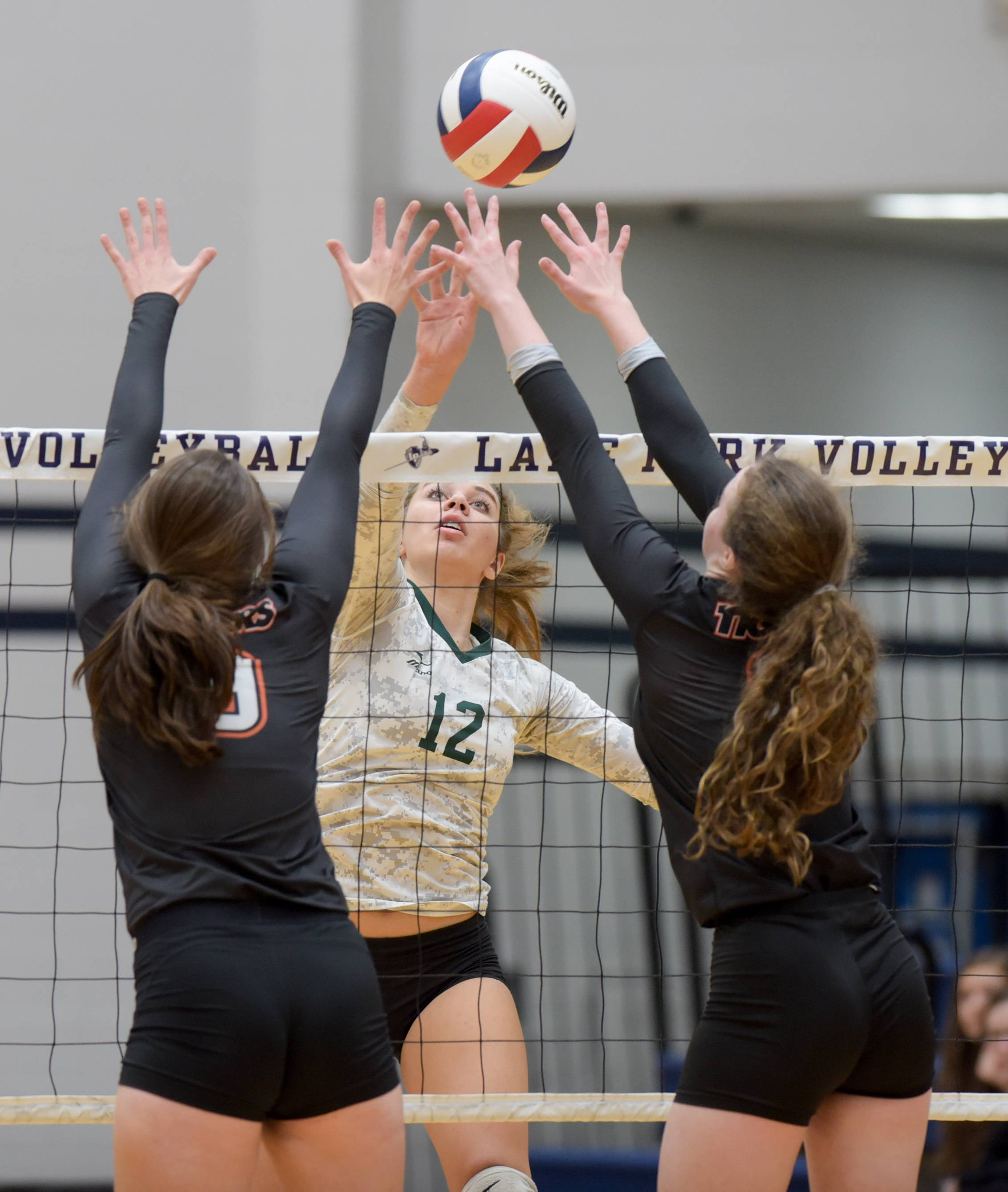 Glenbard West's Nina Crawford taps the ball past Wheaton Warrenville South's Annika Barron and Sarah Burau during Class 4A Lake Park girls volleyball regional final.