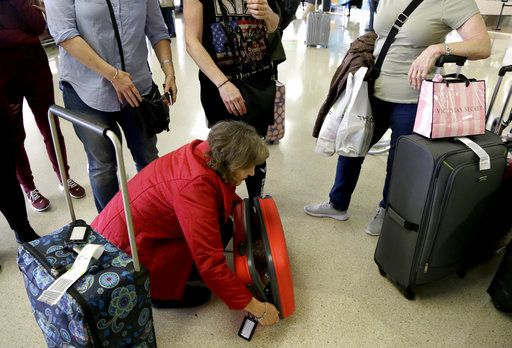 Donna Basquille, of Luton, England, zips up her luggage while talking to acquaintances after meeting them off her flight from London at the international arrival terminal at Newark Liberty International Airport, Thursday, Oct. 26, 2017, in Newark, N.J. Long-haul carriers are starting new screening procedures for U.S.-bound passengers after receiving new security guidelines from American authorities.