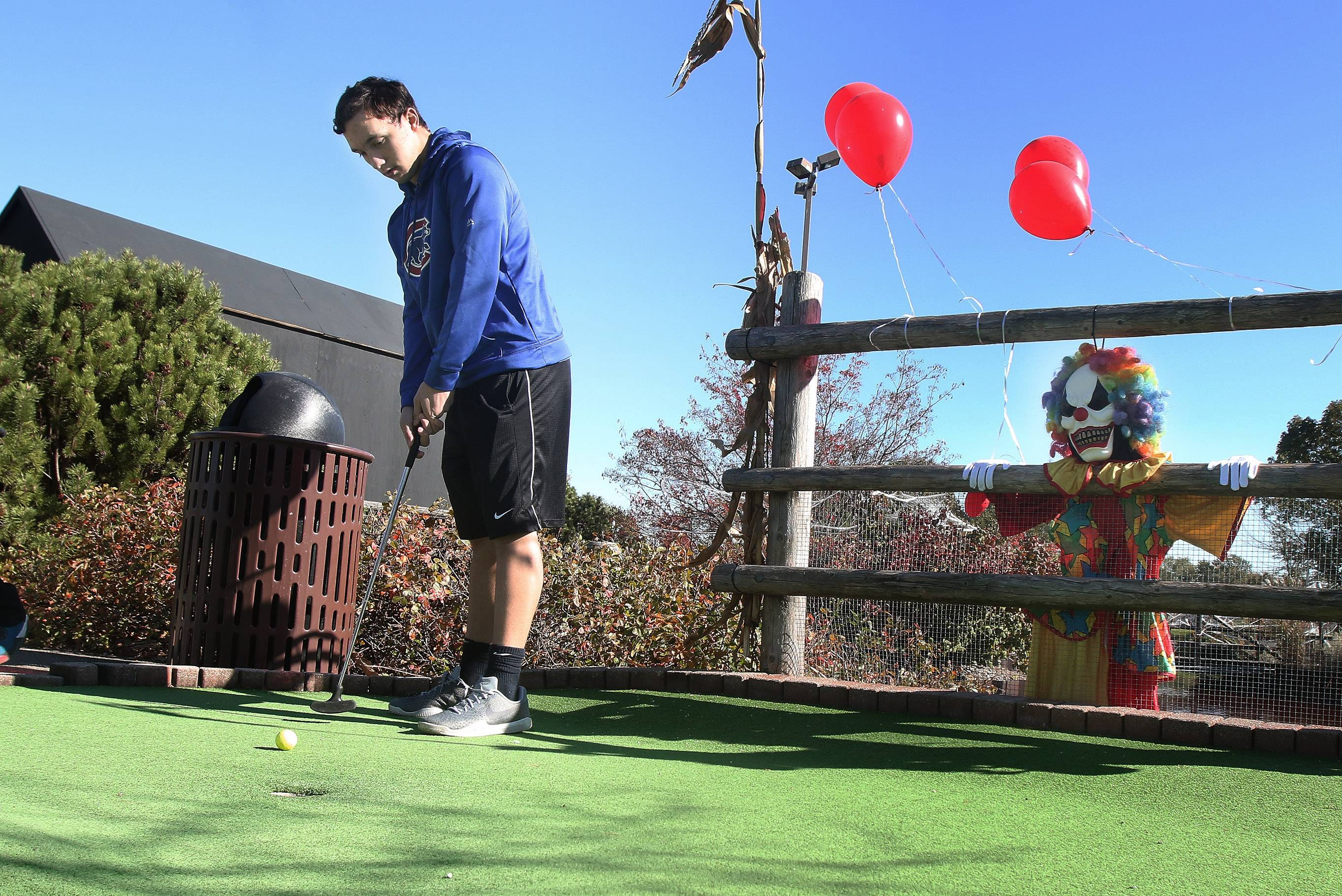 Sixteen-year-old Brett Krambeer of Palatine is under the evil eye of a scary clown as he plays miniature golf during Haunted Hole-A-Ween on Sunday at Mountain View Adventure Center in Des Plaines. Golfers had to navigate around skeletons, ghosts, crazy clowns and vultures as they worked their way around the course.