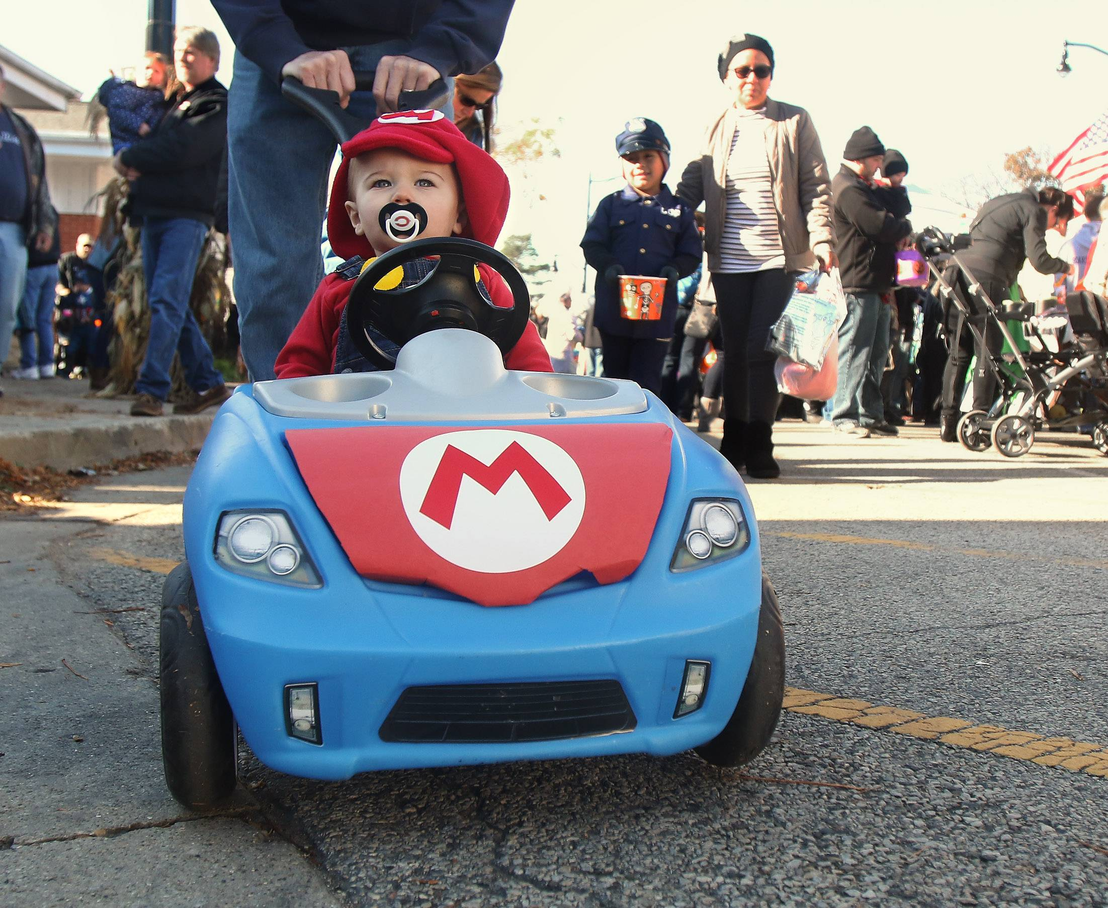 One-year-old Logan Gibson of Wauconda, dressed as Mario, gets a little help driving his car from his grandfather, Russ Slabaugh, during Wauconda's Trick or Treat on Main Street Sunday.