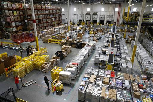In this Aug. 3, 2017, photo, workers prepare to move products at an Amazon fulfillment center in Baltimore. While jobs have been lost in brick-and-mortar stores, many more have been gained from e-commerce and warehousing. Amazon accounts for much of the additional employment. (AP Photo/Patrick Semansky)