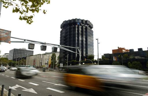 FILE - In this Oct. 6, 2017 file photo, cars drive pass the headquarters of Spanish lender Caixabank in Barcelona, Spain. The tension surrounding Catalonia's push for independence has been a game changer for more than 1,500 companies, including Caixabank, that have moved their official headquarters out of the wealthy region in recent weeks. The companies fear that they will no longer be covered by Spanish and European Union laws if Catalonia manages to secede. (AP Photo/Manu Fernandez, File)