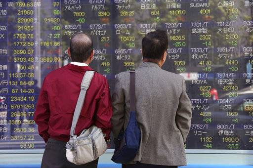 People look at an electronic stock board of a securities firm in Tokyo, Monday, Oct. 30, 2017. Asian stock markets were mixed Monday as investors waited to find out U.S. President Donald Trump's pick to head the Federal Reserve.(AP Photo/Koji Sasahara)