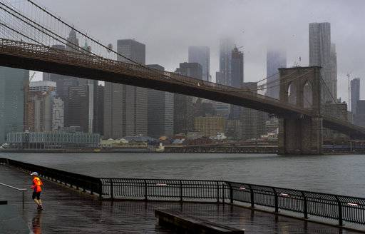 A runner moves along the Brooklyn shoreline of the East River as rain and clouds loom over lower Manhattan on the fifth anniversary of Superstorm Sandy Sunday, Oct. 29, 2017, in New York. (AP Photo/Craig Ruttle)