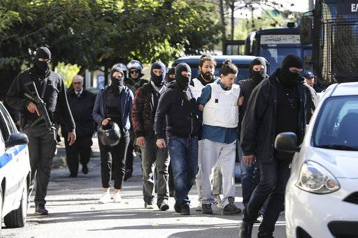 Greek policemen in plain clothes escort suspects to a prosecutor's office in Athens, Sunday, Oct. 29, 2017. Greek police arrested a 29-year-old suspect Saturday in a bomb attack last May on one of the country's former prime ministers. (AP Photo)
