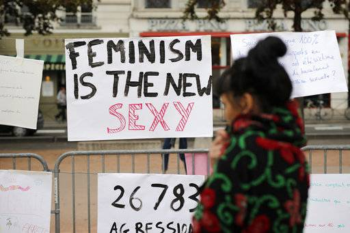 A woman reads a banner during a demonstration to support the wave of testimonies denouncing cases of sexual harassment, in Lyon, central France, Sunday, Oct. 29, 2017. French women are protesting sexual abuse and harassment in 11 cities across the country under the #MeToo banner in the wake of mounting allegations against Hollywood mogul Harvey Weinstein. (AP Photo/Laurent Cipriani)