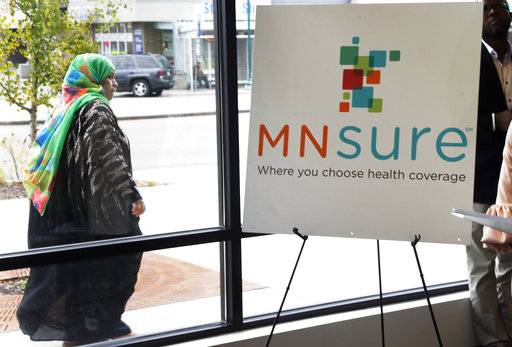 In this Oct. 26, 2017, photo, a woman walks past the Briva Health enrollment office for MNsure, Minnesota's insurance marketplace, in Minneapolis. Health care consumers in most of the country are encountering a world of confusion and chaos as the open enrollment period to sign up for coverage approaches. The outlook is decidedly different in the 12 states that operate their own marketplaces. California, Colorado, Minnesota and other states that operate autonomous exchanges are pulling out all the stops to inform consumers. Briva Health is MNsure's largest enrollment partner. (AP Photo/Jim Mone)