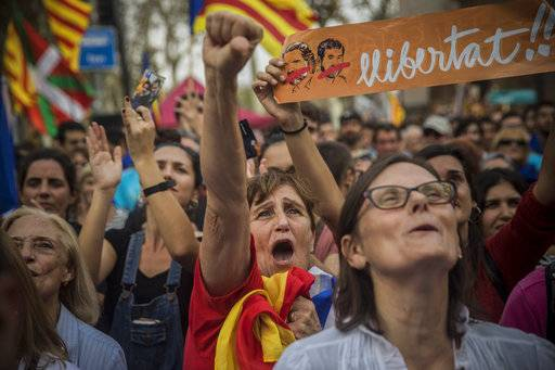 FILE- In this Friday, Oct. 27, 2017 file photo, people react as they watch the parliament session on a huge screen during a rally outside the Catalan parliament in Barcelona, Spain. Pro-independence Catalans are cheering the regional parliament's declaration of secession from Spain, a country they don't regard as their own. (AP Photo/Santi Palacios, File)
