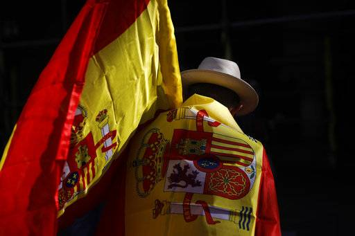 A man wearing a Spanish flag walks along a street ahead of a rally against Catalonia's declaration of independence, in Barcelona, Spain, Sunday, Oct. 29, 2017. Thousands of opponents of independence for Catalonia held the rally on one of the city's main avenues after one of the country's most tumultuous days in decades. (AP Photo/Santi Palacios)