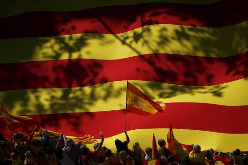 A nationalist activist waves a Spanish flag in front of a giant Catalan flag during a mass rally against Catalonia's declaration of independence, in Barcelona, Spain, Sunday, Oct. 29, 2017. Thousands of opponents of independence for Catalonia are holding the rally on one of the city's main avenues after one of the country's most tumultuous days in decades. (AP Photo/Gonzalo Arroyo)