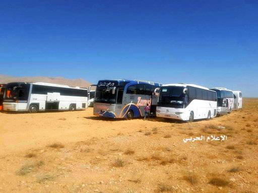 FILE - This file photo provided on Monday, Aug 28, 2017 by the government-controlled Syrian Central Military Media, shows buses gathering before a planned evacuation of Islamic State group militants, in the mountainous region of Qalamoun, Syria. Islamic State militants, routed from one urban stronghold after another in Syria, have recently been moving deeper into Syria's remote desert where experts say they are regrouping and preparing their next incarnation.(Syrian Central Military Media via AP, File)