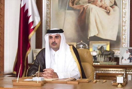 FILE- In this Friday, July21, 2017, file photo, Emir of Qatar Sheikh Tamim bin Hamad Al Thani talks in his first televised speech since the dispute between Qatar and three Gulf countries and Egypt, in Doha, Qatar. Qatar's emir has warned against any military confrontation over the ongoing diplomatic dispute between his country and four other Arab nations, saying it will only engulf the region in chaos. (Qatar News Agency via AP, File)