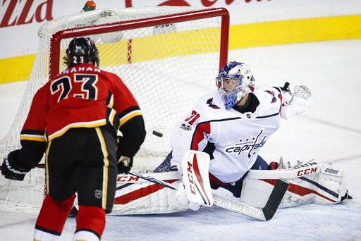 Washington Capitals goalie Philipp Grubauer (31), from Germany, looks back as Calgary Flames center Sean Monahan (23) scores during the third period of an NHL hockey game in Calgary, Alberta, Sunday, Oct. 29, 2017. The Flames won, 2-1. (Jeff McIntosh/The Canadian Press via AP)