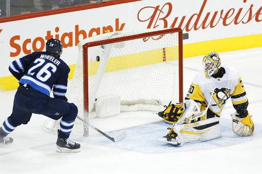Winnipeg Jets right wing Blake Wheeler (26) scores on Pittsburgh Penguins goalie Matthew Murray (30) during the first period of an NHL hockey game in Winnipeg, Manitoba, Sunday, Oct. 29, 2017. (John Woods/The Canadian Press via AP)