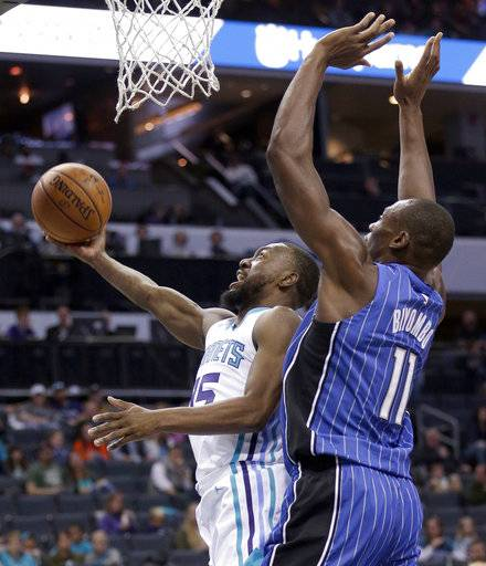 Charlotte Hornets' Kemba Walker (15) drives past Orlando Magic's Bismack Biyombo (11) during the first half of an NBA basketball game in Charlotte, N.C., Sunday, Oct. 29, 2017. (AP Photo/Chuck Burton)