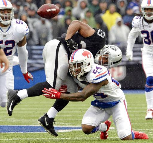 Oakland Raiders running back DeAndre Washington (33) fumbles the ball as he is hit by Buffalo Bills defensive back Leonard Johnson (24) during the first half of an NFL football game, Sunday, Oct. 29, 2017, in Orchard Park, N.J. (AP Photo/Adrian Kraus)