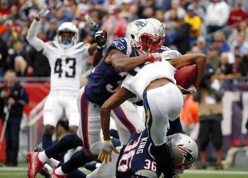 New England Patriots' Jonathan Jones top and Brandon King (36) tackle Los Angeles Chargers punt returner Travis Benjamin (12) in the end zone for a safety during the first half of an NFL football game, Sunday, Oct. 29, 2017, in Foxborough, Mass. (AP Photo/Michael Dwyer)