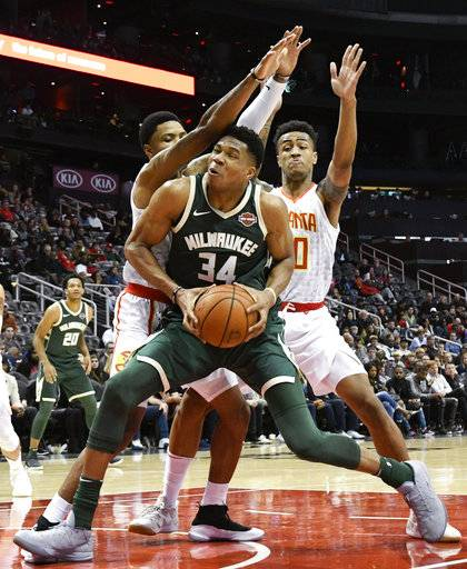 Milwaukee Bucks forward Giannis Antetokounmpo (34) drives into the lane as Atlanta Hawks forward Kent Bazemore, left, and forward John Collins, right, defend during the second half of an NBA basketball game, Sunday, Oct. 29, 2017, in Atlanta. (AP Photo/John Amis)
