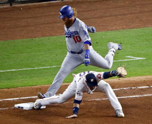Los Angeles Dodgers' Justin Turner is forced out at first by Houston Astros first baseman Yuli Gurriel during the seventh inning of Game 4 of baseball's World Series Saturday, Oct. 28, 2017, in Houston. (AP Photo/Charlie Riedel)