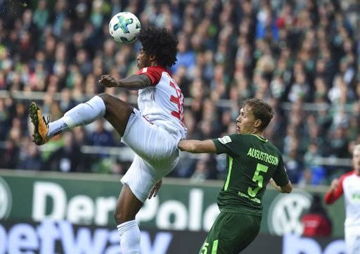 Augsburg's Caiuby , left, and Bremen's Ludwig Augustinsson challenge for the ball during the German Bundesliga soccer match between SV Werder Bremen and FC Augsburg, in Bremen, Germany, Sunday, Oct. 29, 2017. (Carmen Jaspersen/dpa via AP)