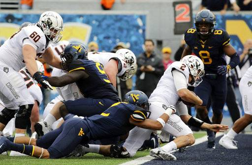 Oklahoma State quarterback Mason Rudolph (2) runs the ball for a touchdown as West Virginia safety Kenny Robinson (2) tries to stop him during the first half of an NCAA college football game, Saturday, Oct. 28, 2017, in Morgantown, W.Va. (AP Photo/Raymond Thompson)