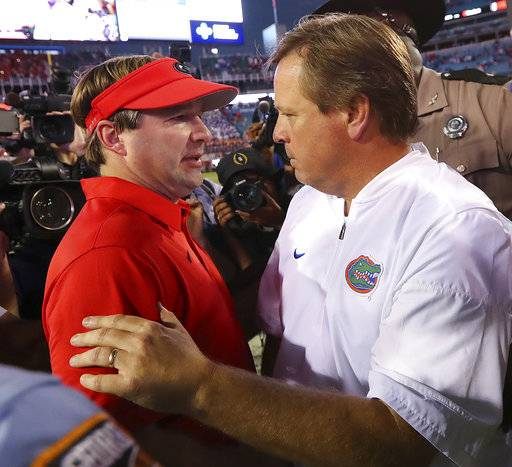 Georgia head coach Kirby Smart,left, and Florida head coach Jim McElwain meet at midfield after Georgia beat Florida 42-7 an NCAA college football game, Saturday, oct. 28,, 2017, in Jacksonville, Fla. (Curtis Compton/Atlanta Journal-Constitution via AP)