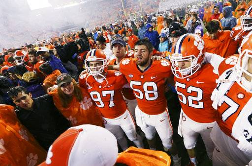 Clemson players join with fans to sing the school fight song after defeating Georgia Tech 24-10 in an NCAA college football game Saturday, Oct. 28, 2017, in Clemson, S.C. (AP Photo/John Bazemore)