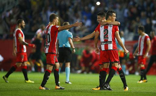 Girona's Bernardo Espinosa, (2) is hugged by teammate �lex Granell as they celebrate after the end of the La Liga soccer match between Girona and Real Madrid at the Montilivi stadium in Girona, Spain, Sunday, Oct. 29, 2017. Girona defeated Real Madrid 2-1. (AP Photo/Manu Fernandez)