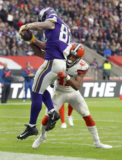 Minnesota Vikings tight end Kyle Rudolph, left, catches a 4-yard touchdown pass as Cleveland Browns cornerback Mike Jordan (41) defends during the second half of an NFL football game at Twickenham Stadium in London, Sunday Oct. 29, 2017. (AP Photo/Tim Ireland)